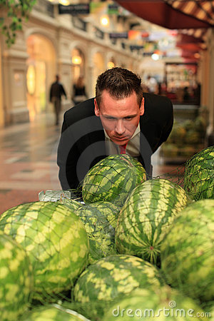 Man smelling watermellons in shopping-centre