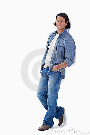 Man smiling while leaning against a wall
