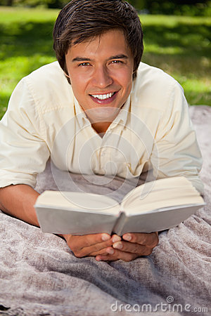 Man smiling while reading a book as he lies on a blanket
