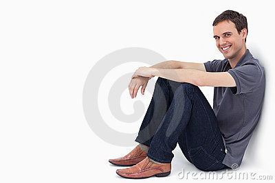 A man smiling while sitting against a wall