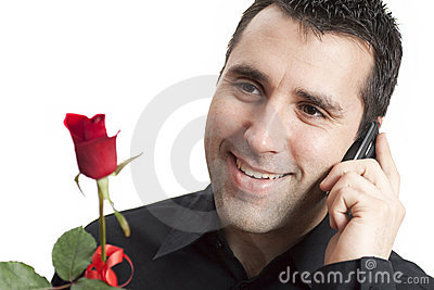 Man smiling, talking on cellphone, holding red ros