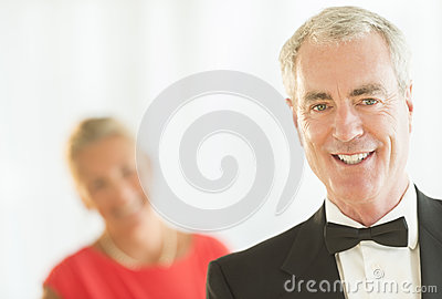 Man Smiling With Woman In Background At Home