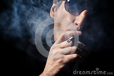 The man smokes a cigaret