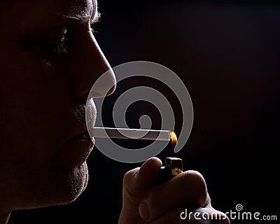 The man smokes a cigarette