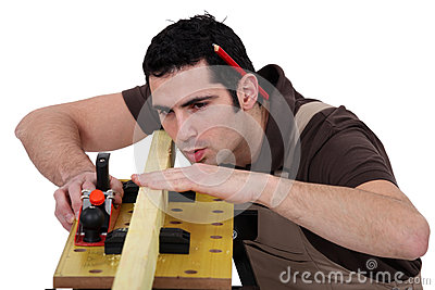 Man smoothing plank of wood