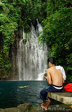 Man SMS-ing near tropical waterfall.