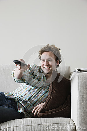 Man On Sofa With TV Remote Control