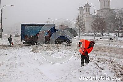 Man som arbetar på snöborttagning Redaktionell Arkivfoto