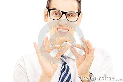 Man som bryter en cigarett och gör en gest avslutat röka