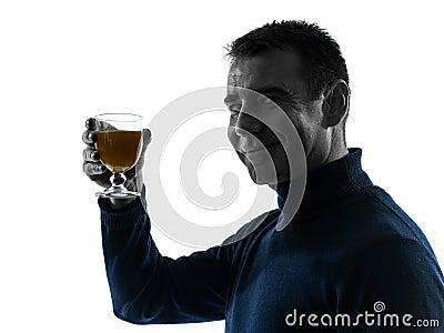 Man som dricker den orange fruktsaftsilhouetteståenden