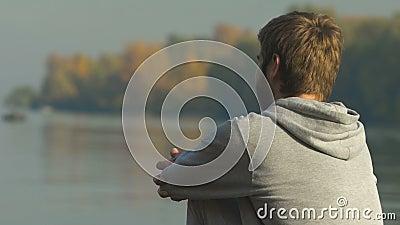 Man som sitter på flodbanken som ser vatten som tänker om hans framtid, plan stock video