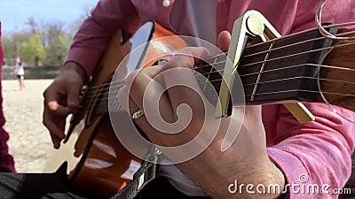 Man som spelar gitarren med sommar för ferie för fri tid för klassiskt ackord för musiker för ultrarapidforsmusik akustisk Bruk f lager videofilmer