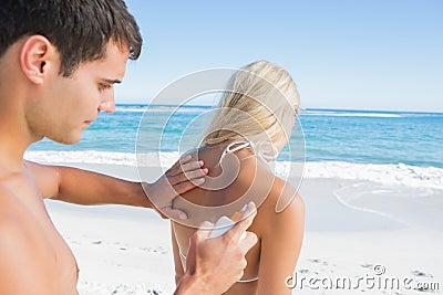 Man som tillbaka sätter solkräm på flickvänner