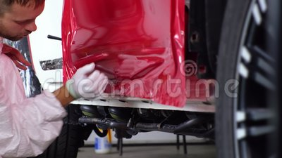 Man specialist is fixing protective vinyl sheath on car body. In auto service stock video