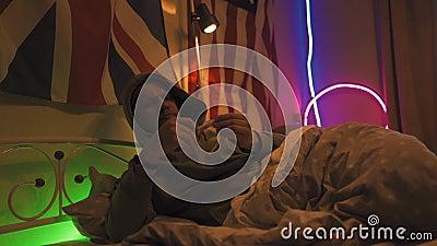 Man spielt auf Tablette, während man auf dem Bett in einem Hoodie liegt, legt es zur Seite und nimmt das Thermometer unter seine  stock footage