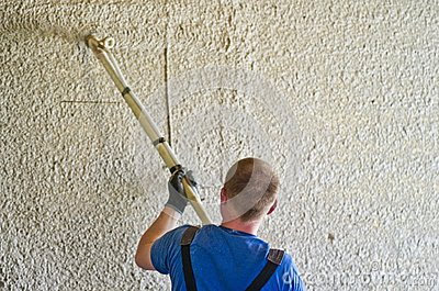 Man spraying concrete stucco to wall