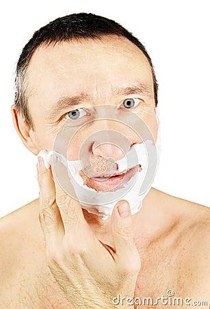 Man spreads shaving foam on his cheeks