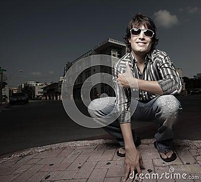 Man squatting on the street