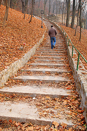 Man on stairs covered with leaves