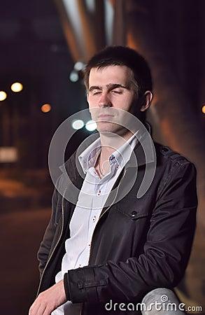 Man is standing alone on night bridge