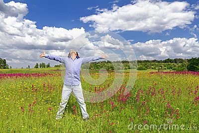 Man standing on a meadow on blue sky background