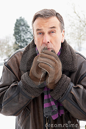 Man Standing Outside In Snow Warming Hands