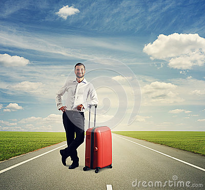 Man standing with suitcase on the road