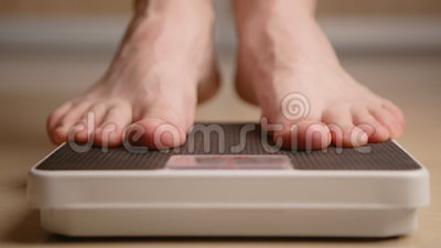 A man standing on weight scale stock video footage