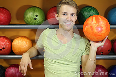 Man stands near shelves with balls in bowling club