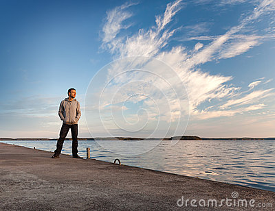 A man stands on the pier starring at the sea