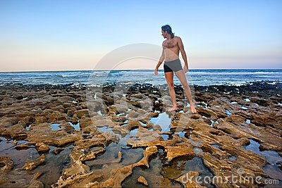 Man stands on rocky beach