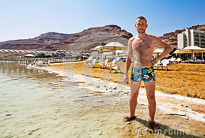 A man stands on the shore of the dead sea