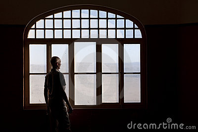 Man staring out a dirty window