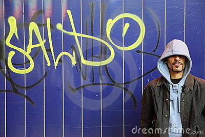 Man is staying near wall with graffiti in a street