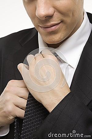 Man straightening necktie