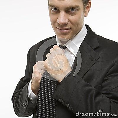 Man straightening necktie.