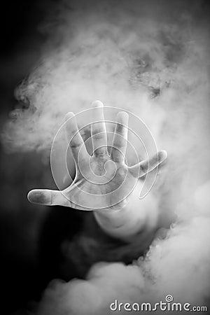 Man stretching hand through smoke