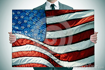 Man in suit holding an american flag