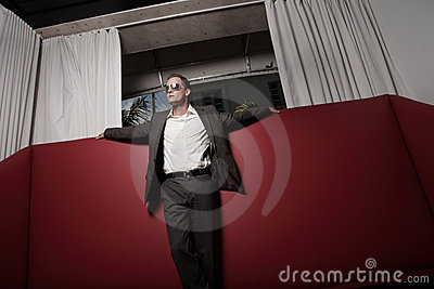 Man in a suit on a red leather couch