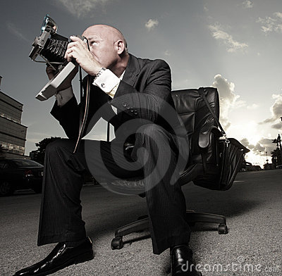 Man in a suit sitting and photographing