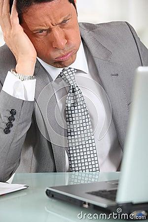 Man in suit staring at laptop