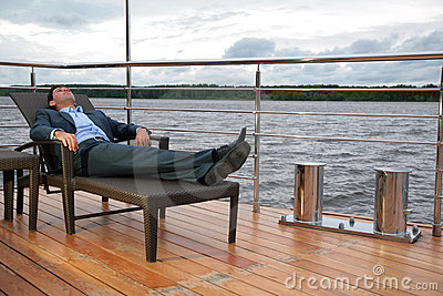 Man in suit, who rests in chaise lounge on  wharf