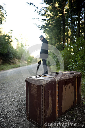 Man with suitcase hitchhiking in a rural road