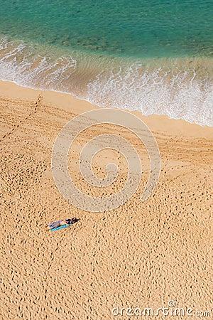 Man sun bathing solo on secluded beach
