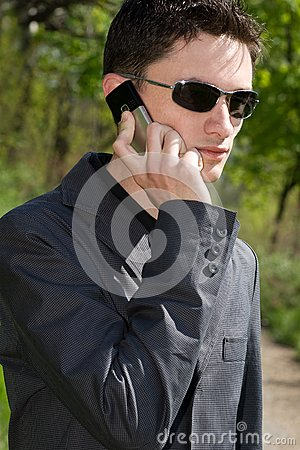 Man in sunglasses and jacket talks on cell phone