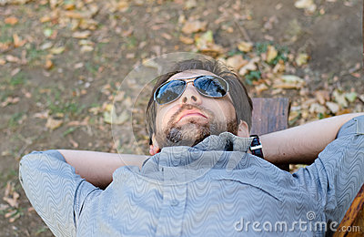 Man with sunglasses lying on bench