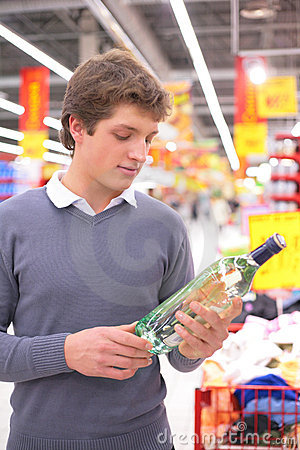 Man in supermarket with bottle of alcohol