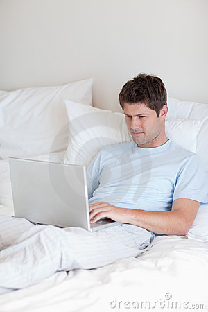 Man surfing the internet in bed