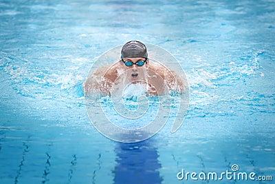 Man swimmer in cap taking breath