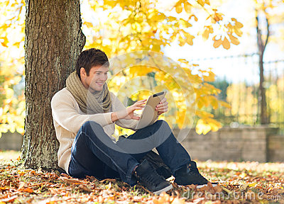 Man with tablet pc in autumn park